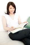 Cheerful woman reading a book sitting on a sofa Stock Image