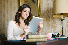 Cheerful woman reading on digital tablet at home Royalty Free Stock Images