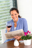 Cheerful woman reading drinking wine newspaper living Stock Image