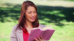 Cheerful woman reading an interesting novel. In the countryside stock footage