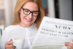 Cheerful woman reading newspaper. Stock Photo