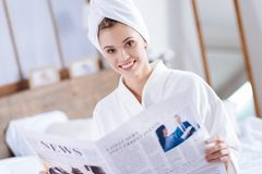 Cheerful woman reading newspaper after shower royalty free stock photos