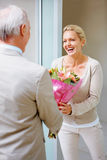 Cheerful woman receiving bouquet from her  husband Royalty Free Stock Image