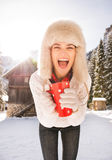 Cheerful woman with red cup standing near cosy mountain house Stock Photography
