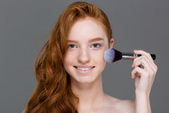 Cheerful woman with red hair doing make up on cheeks Royalty Free Stock Photos