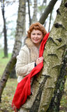 The cheerful woman with a red scarf costs having leaned against a birch in the wood.  Royalty Free Stock Image