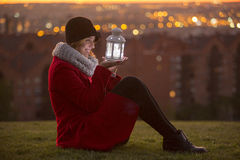 Cheerful woman on a red winter coat holding a led lights lantern Stock Photo