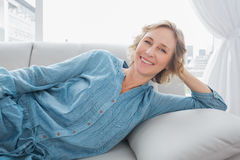 Cheerful woman relaxing on her couch Royalty Free Stock Image