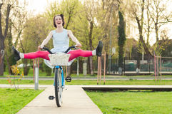 Cheerful woman riding bicycle with her legs in the air Royalty Free Stock Photo