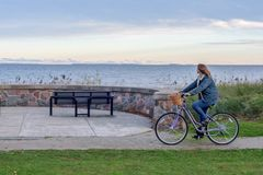 Cheerful woman riding bike along Lake Superior shoreline in fall. Riding bicycle along Lake Superior shoreline in Upper Michigan in Autumn stock photos