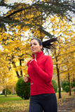 Cheerful woman running in autumn park Stock Photos