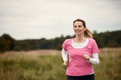 Cheerful woman running through the fields. Cheerful woman running through field in fall, copy space to the left Stock Photography
