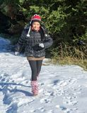 A cheerful woman running in a snowy nature. royalty free stock image