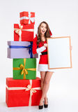 Cheerful woman in santa claus cloth holding blank board Stock Photos