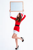 Cheerful woman in santa claus cloth holding blank board. Full length portrait of a cheerful woman in santa claus cloth holding blank board over head  on a white Royalty Free Stock Image