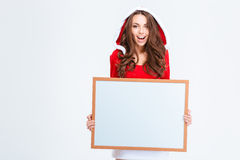 Cheerful woman in santa claus cloth holding blank board Royalty Free Stock Images
