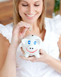 Cheerful woman saving money in a piggy-bank. At home Stock Images
