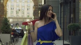 Cheerful woman with shopping bags talking on phone stock video footage