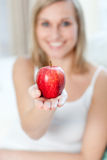 Cheerful woman showing an apple Royalty Free Stock Images