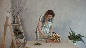 Cheerful woman showing assembled edible bouquet. Positive redhead woman in apron showing tasty assembled edible arrangement with assorted types of cheese, cherry stock video footage