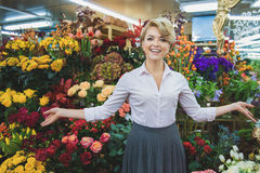 Cheerful woman showing bouquets in store Royalty Free Stock Images
