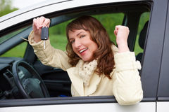 Cheerful woman showing car keys. Beautiful happy woman sitting in a car and showing keys out the window Royalty Free Stock Photography