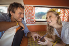 Cheerful woman showing mobile phone to man in van Stock Image