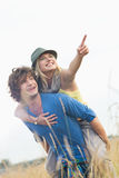 Cheerful woman showing something while enjoying piggyback ride on man in field. Cheerful women showing something while enjoying piggyback ride on men in field Royalty Free Stock Images