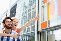 Cheerful woman showing something to man while enjoying piggyback ride in city Royalty Free Stock Photo