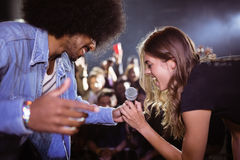 Cheerful woman singing with male singer at nightclub stock photography