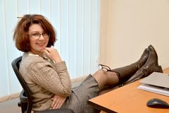 The cheerful woman sits at office with legs on a table and glasses on a knee Royalty Free Stock Photo
