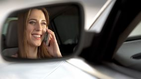 Cheerful woman sitting in automobile and talking on smartphone with parents. Stock photo royalty free stock image