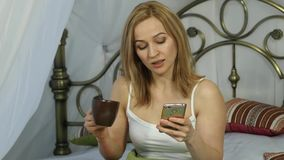 Cheerful woman sitting in bed dancing and singing, drinking coffee and chatting with friends on a phone. 4K stock video