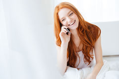Cheerful woman sitting in bed and talking on mobile phone Royalty Free Stock Photo