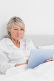 Cheerful woman sitting in bed using tablet pc Royalty Free Stock Image