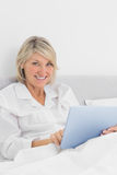 Cheerful woman sitting in bed using tablet pc looking at camera Stock Photos