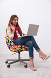 Cheerful woman sitting on the colourful chair Royalty Free Stock Photos