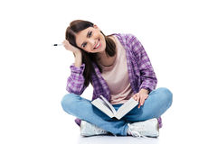 Cheerful woman sitting on the floor with books Stock Photo