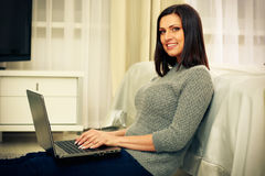 Cheerful woman sitting on the floor with laptop Stock Photos