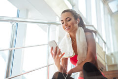 Cheerful woman sitting in gym and listening to music stock images