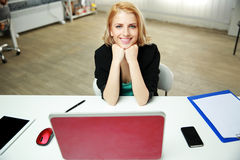 Cheerful woman sitting at her work place Stock Image