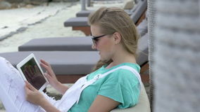 Cheerful woman sitting in hotel lounger using digital tablet during vacation. Young blonde woman reading e-book in tropical resort. Woman relaxing on luxury stock video