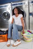 Cheerful Woman Sitting In Laundry Stock Photography