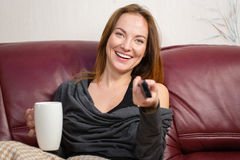 Cheerful woman sitting in living room with tv remote control Royalty Free Stock Photo