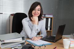 Cheerful woman sitting in the office in front of laptop. Woman sitting in the office in front of laptop Stock Photos