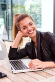Cheerful woman sitting at outdoor cafe with laptop Royalty Free Stock Photo