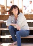 Cheerful woman sitting outdoors on steps Royalty Free Stock Photography