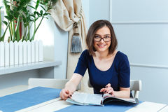 Cheerful woman sitting and reading magazine in cafe Stock Image