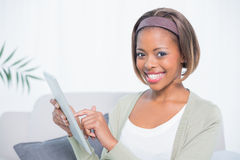 Cheerful woman sitting on sofa using her tablet Royalty Free Stock Photography