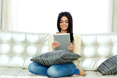 Cheerful woman sitting on the sofa and using tablet computer Royalty Free Stock Photography